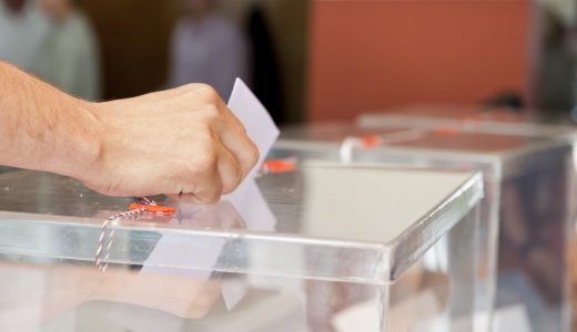 Unrecognizable person putting paper in sealed  transparent box, voting for elections, shallow doff