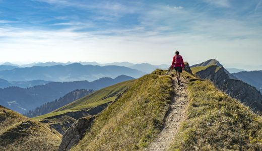 nice senior woman, hiking in fall, autumn  on the ridge of the Nagelfluh chain near Oberstaufen, Allgaeu Area, Bavaria, Germany, Hochgrats summit in the background